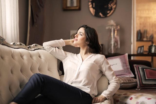 žena na bílé pohovce u okna